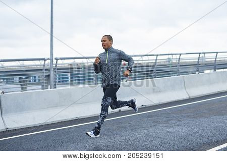 Black male runner exercising outdoors. Handsome fashionable young Afro American sportsman running preparing for marathon doing high intensity interval training sprint workout . Freeze action shot