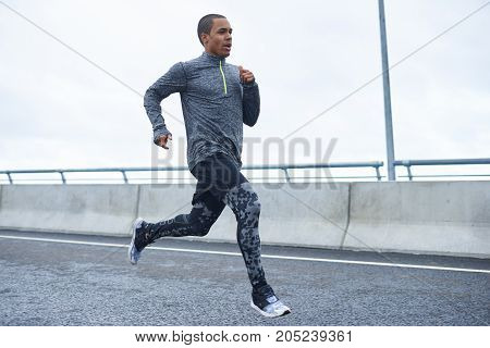 Freeze action shot of confident young black athletic man wearing trendy running shoes and sports clothes exercising outdoors. Picture of dark-skinned sportsman running on autumn day at stadium