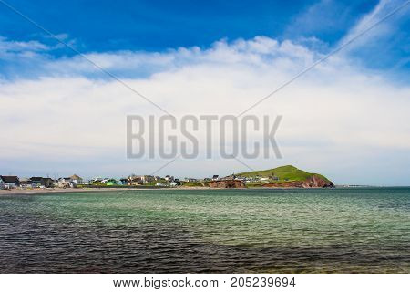 Distant sandy beach with houses blue sky and sea as foreground at Magdalen Island.