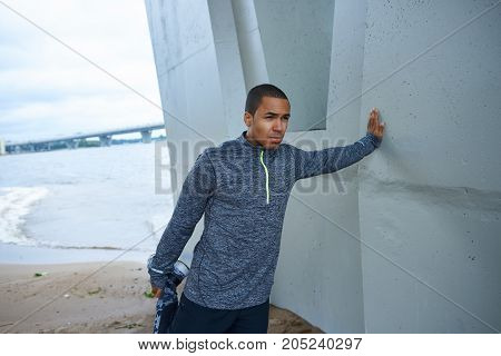 Picture of black young male jogger dressed in trendy outfit stretching legs before running exercise outdoors leaning on grey wall of concrete construction having determined confident look