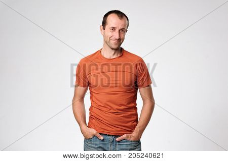 Smiling mature caucasian man standing with arms in pockets against gray background
