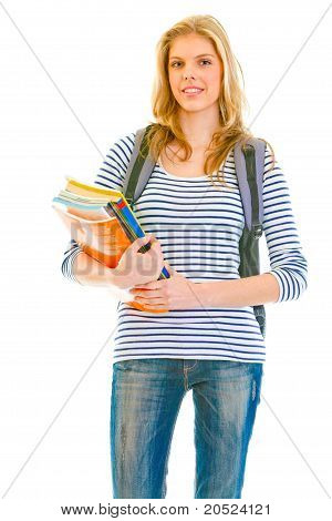 Smiling young girl with schoolbag holding schoolbooks in hands isolated on white