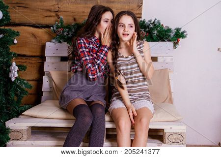 Two sisters share secrets the girl tells a secret in the ear of his sister girlfriend