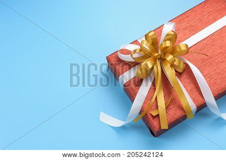 Red gift box with gold and white ribbon bow on blue background top view