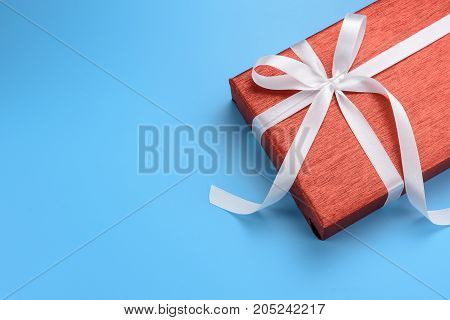 Red gift box with white ribbon on blue background top view