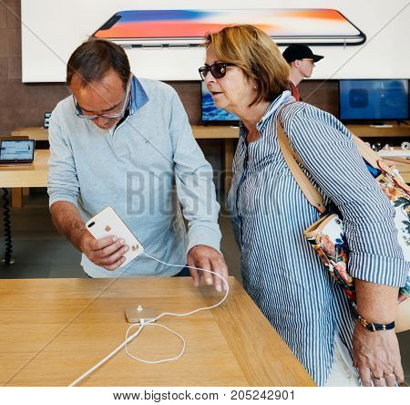PARIS FRANCE - SEP 22 2017: New iPhone 8 and iPhone 8 Plus as well the updated Apple Watch Apple TV goes on sale today in Apple Store with senior couple looking at the latest iphones