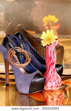 Sexy blue suede high heels, bracelets, pink vase and yellow flower sitting on gold foil.