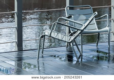 Two Outdoor Gray Metal Chairs Stand On Pier