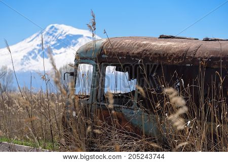 Abandoned and rusty old Soviet Russian bus in the middle of reeds and agriculture fields with snow-capped scenic Ararat mountain and clear blue sky on the background in rural Southern Armenia in Ararat province on 4 April 2017.