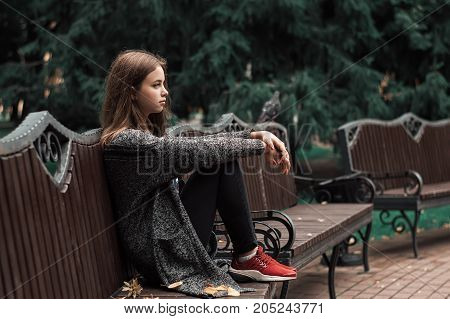 Teenage girl sitting on the wooden bench in the park. Young female with brown hair in warm grey cardigan and black jeans. Autumn mood