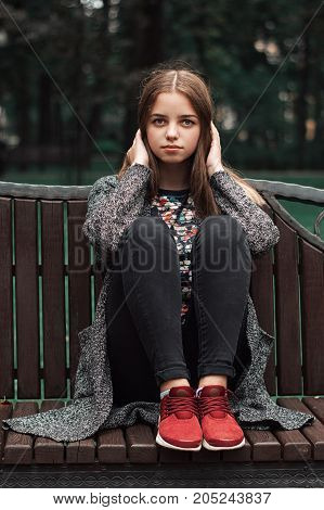 Vertical photo of female teenager sitting on wooden bench in the park. Young model posing outdoors