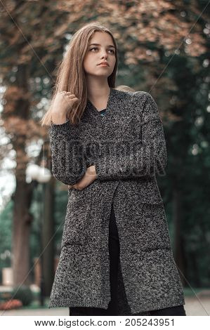 Young female with blond hair in warm knitted cardigan of grey color standing in autumn park. Vertical portrait of teenage girl
