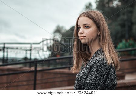 Portrait of teenage female with blue eyes and blond hair in grey knitted handmade jacket