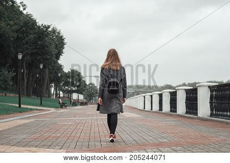 Female teenager with black backpack black denim trousers and grey knitted cardigan walking in the park
