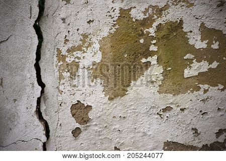 The close up of a wall with a chipped plaster layer.