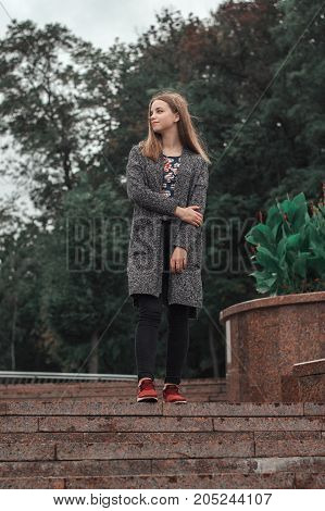 Vertical photo of teenage girl in knitted long jacket and black denim trousers standing at the stairs in the park
