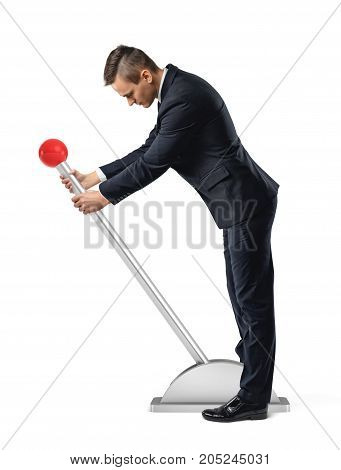 A businessman stands at a large lever with a red round knob and starts to move it. Start your business. Jump-start your career. Hands-on approach.