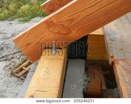 Waterproofing wooden roof truss with bitumen membrane against water. Building house roofing construction.