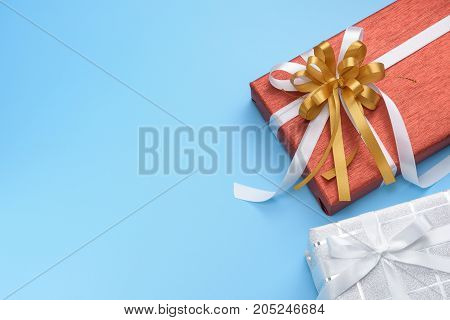 Red and white gift boxes with ribbon on blue background top view