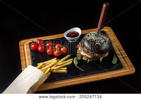 Black double hamburger made from beef with jalapeno pepper, cheese and vegetables. Nearby is French fries and cherry tomatoes.
