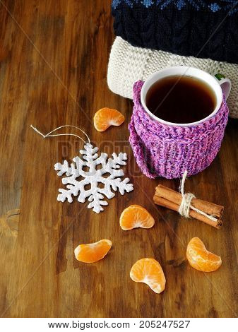 Tea in a mug wrapped into tiny scarf surrounded by mandarin segments on a wooden background