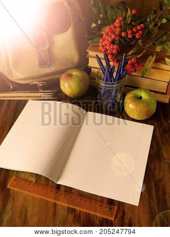 Open paper notebook with school supplies and apples in the background. The notebook is lying on a wooden table. Photo with special editing