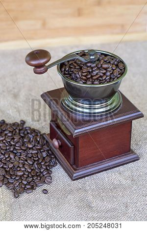 Coffee grinder full of roasted coffee beans and coffee beads on the right side - from the top