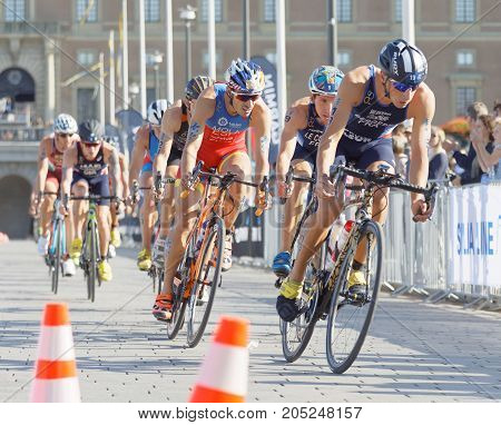 STOCKHOLM - AUG 26 2017: Mario Mola (ESP) and group of fighting male triathlete cyclists royal castle in the background in the Men's ITU World Triathlon series event August 26 2017 in Stockholm Sweden