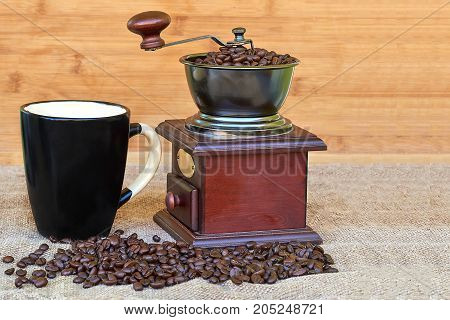 Coffee grinder full of roasted coffee beans and black mug