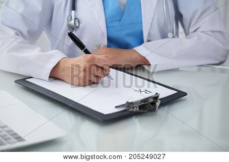Doctor woman filling up prescription, close-up of hands. Physician at work. Medicine and healthcare concept.