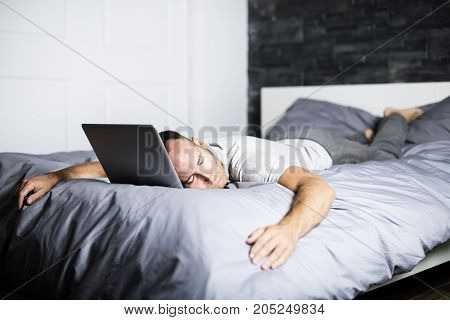 A man sleeping over laptop computer in bed