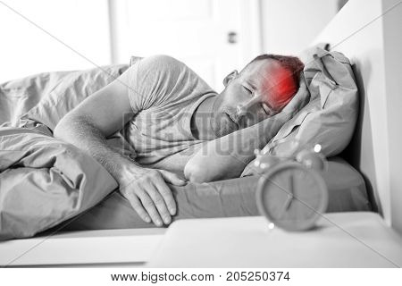 A Portrait of Young Caucasian man in bed with headache