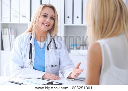 Doctor and  patient  discussing something while sitting at the table . Medicine and health care concept.