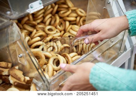 Woman Buyer In Shop Buys Bagels Using Scoop For Products