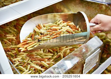 Buyer picks up colored pasta in a tray at the store using a metal scoop