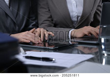 Group of businesspeople or lawyers at meeting. Close-uo of human hands at work. Low key lighting.