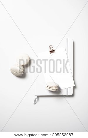 White flat lay with beige macaroons, notepad and postcard mockup on white table background