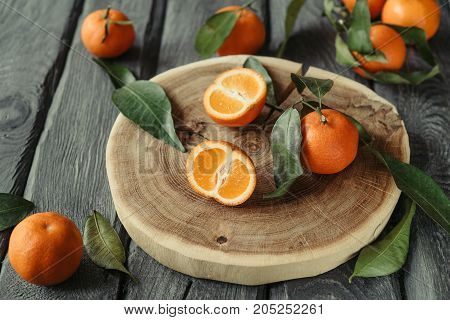 Macro Photo Of A Cutted Mandarin With Green Leaves On A Black Wooden Table. Tasty Tangerines For The