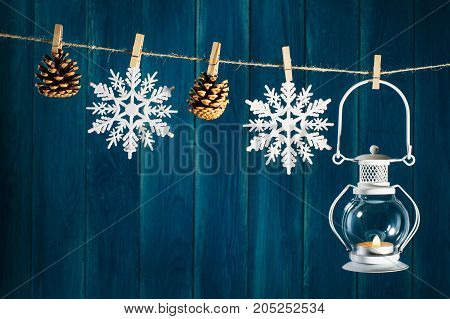 Christmas background. Candle lantern fir cones and snowflakes on clothespin on deep blue wooden background with copy space. Christmas or New Year card template.