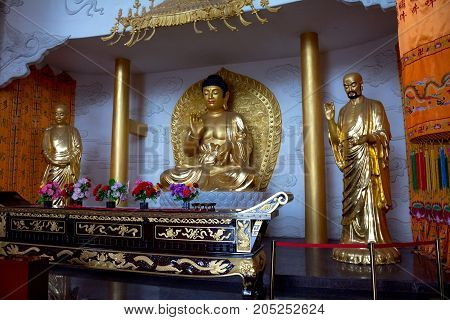 A golden buddha in a lotus pose. Subject of Chinese religion, Buddhism, Asia, Leshan Shi
