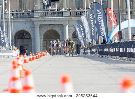 STOCKHOLM - AUG 26 2017: Distant group of fighting male triathlete cyclists royal castle in the background in the Men's ITU World Triathlon series event August 26 2017 in Stockholm Sweden
