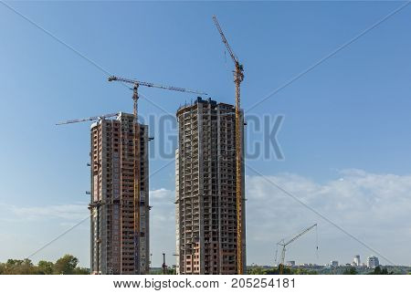 Two multi-storey buildings under construction. Many cranes. Construction of modern housing. Building bussiness.