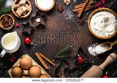 Christmas Baking background. Ingredients for cooking christmas baking on dark stone background. Top view with copy space.