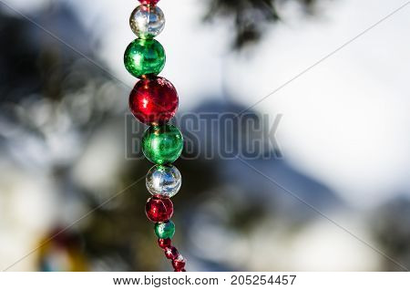 Red Green and Silver Christmas Ornament Beads Decorating a Snowy Outdoor Tree