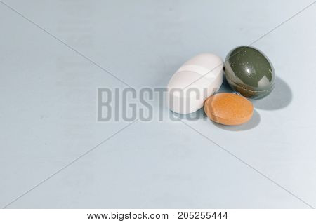 group of three pills over a pale blue background with copys space on the left. pharmaceutical. disease. cure. medicine