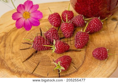Red fresh raspberries on brown rustic wood background  with beautiful structure.. Natural ripe organic berries with peduncles on wooden table.
