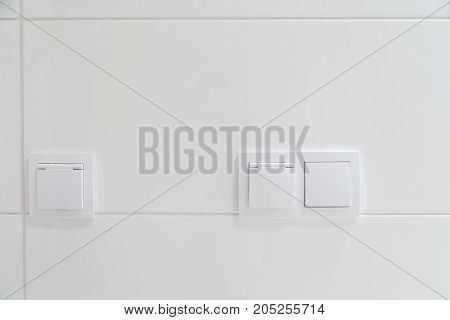 Modern electrical switches on a white wall of tiles.