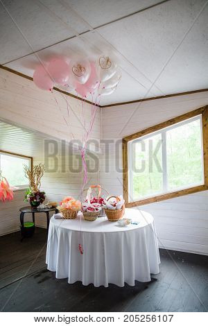 table serving with baskets, flowers and balloons in bright hall
