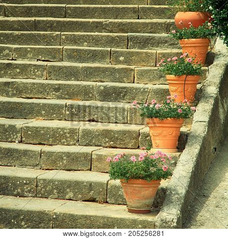 Old stone steps decorated by flower pots in small italian town, Italy. Square toned image. Selective focus