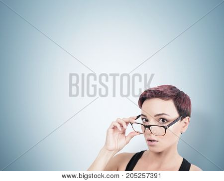 Close up portrait of a young surprised woman with short red hair taking off her glasses. Gray background. Concept of strong emotions Mock up